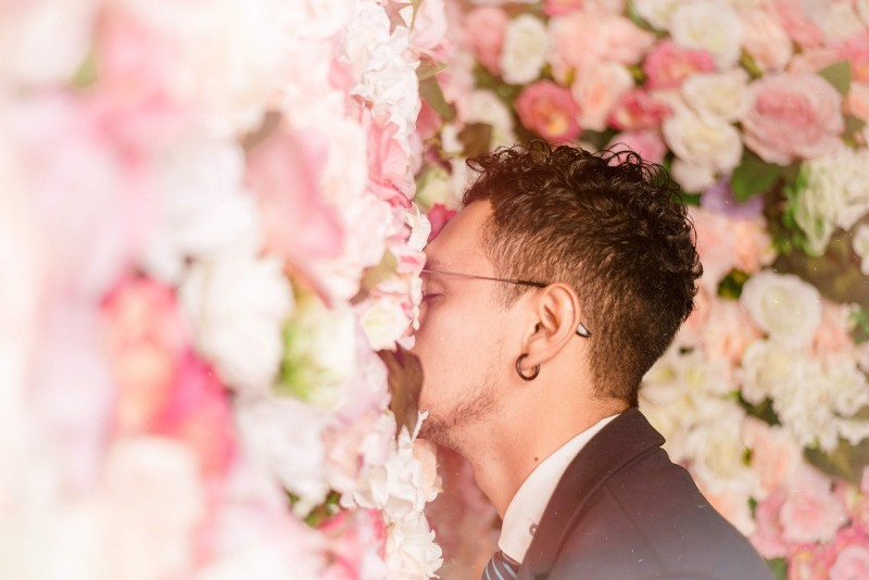 man smelling wedding flowers