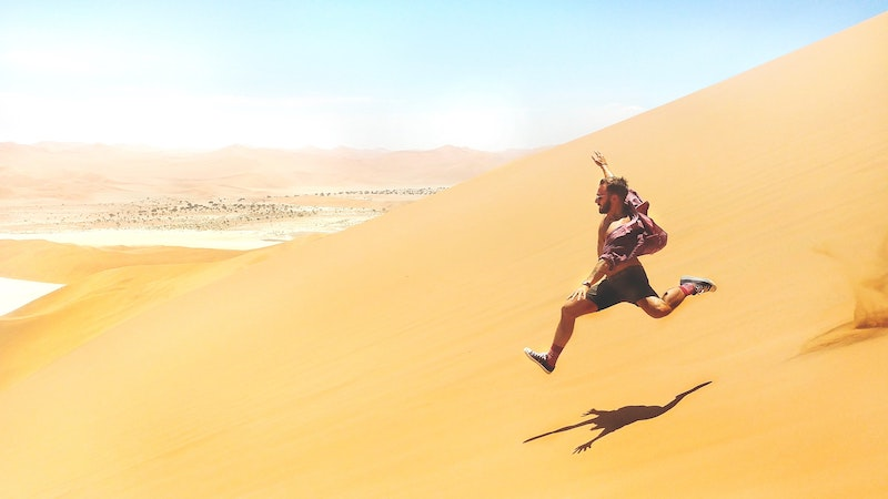 man running down side of sand dune