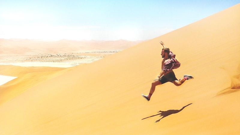 man running down side of sand dune