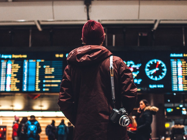 man at airport looking at departure board
