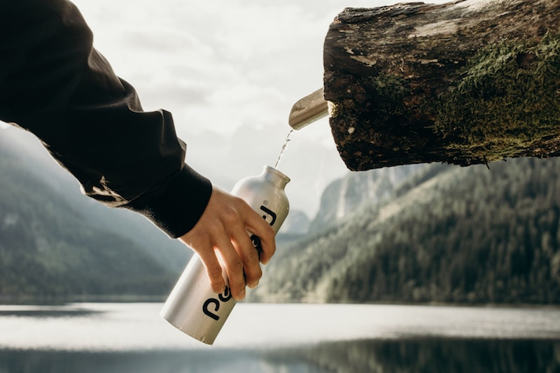 man collecting mineral water from rock