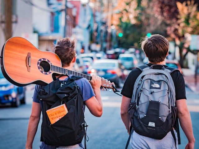 men walking down street with guitar
