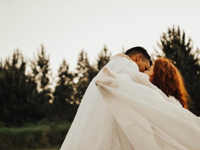 man and woman kissing under sheet