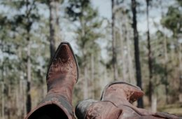 view of cowboy boots and forest in background