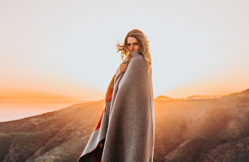 woman in blanket with sunset behind