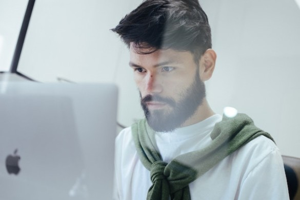 bearded man looking at computer screen