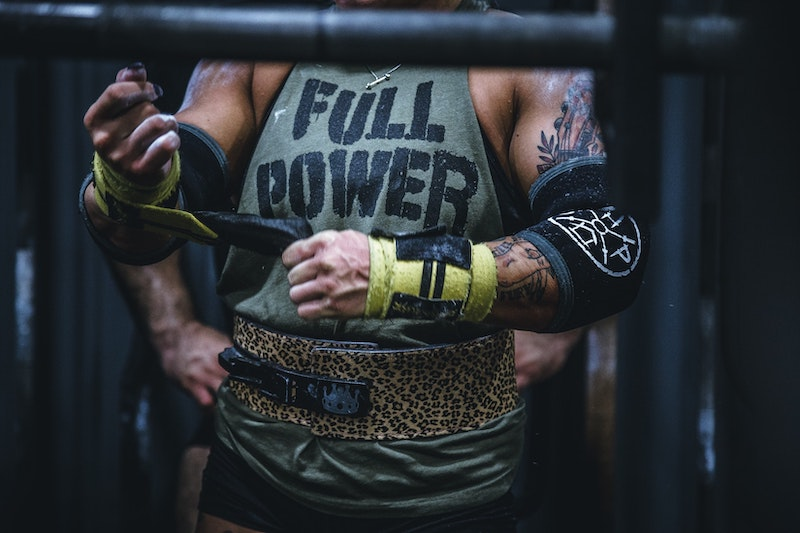 powerlifter wrapping wrists with wrist straps