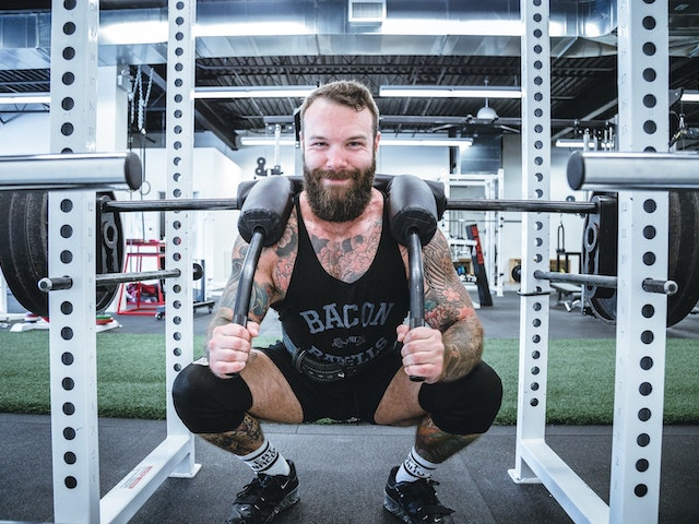 man doing squat with powerlifting accessories on