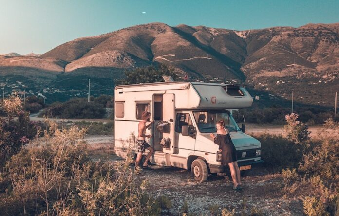 RV in the country with mountains in the background and a girl and guy near the RV