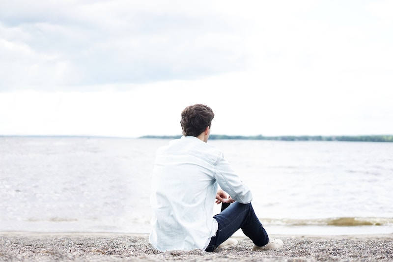 man sitting on beach looking at body of water