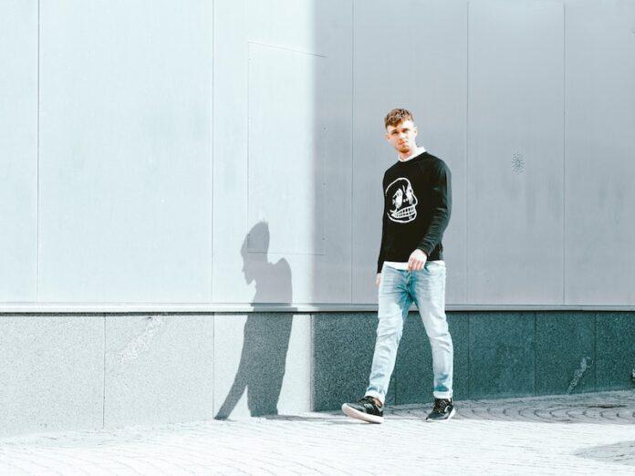 Man walking in front of concrete wall black jumper on