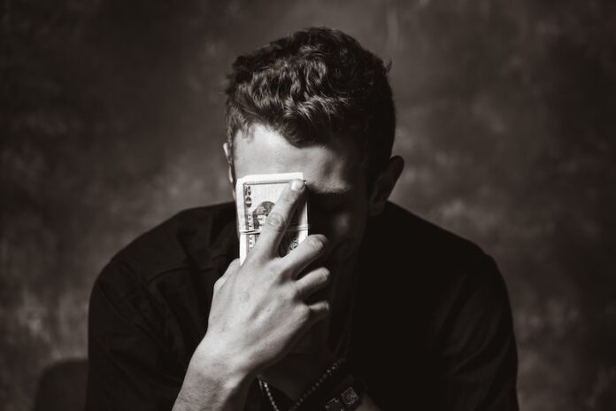 Black and white photo man holding money to his face