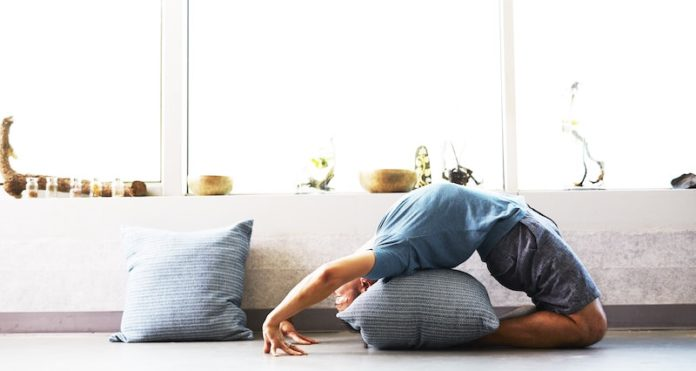 man stretching at home staying healthy during coronavirus lockdown